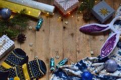 Begreppsmässig vinterbild Hemtrevlig julram med gåvor, Xmas-garneringar, tumvanten, godis på träbakgrund kopiera avstånd ställe Royaltyfria Foton