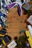 Begreppsmässig vinterbild Hemtrevlig julram med gåvor, Xmas-garneringar, tumvanten, godis på träbakgrund kopiera avstånd ställe Arkivbild