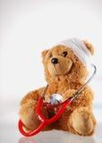 Begreppsmässiga sjuka Teddy Bear med stetoskopapparaten arkivbilder