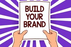 Begreppsmässigt byggande för handhandstilvisning ditt märke Affärsfototext gör ett kommersiellt papper pag för identitetsmarknads stock illustrationer