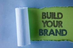 Begreppsmässigt byggande för handhandstilvisning ditt märke Affärsfototext skapar din egen logosloganmodell som annonserar e-mark royaltyfria bilder