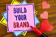 Begreppsmässigt byggande för handhandstilvisning ditt märke Affärsfototext skapar din egen logosloganmodell som annonserar e-mark arkivfoto