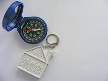 Begreppsmässigt hus och kompass på vit bakgrund med stället för att skriva royaltyfria foton