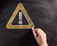 Begreppsmässigt varningstecken på den svarta svart tavlan Royaltyfria Foton