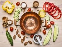 Begreppsmatlagningsallad av olika kryddor och örtgrönsaker som ut läggas runt om kopparbunkar för sallad, ställe för text Arkivbilder