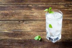 Begreppsmeny för drinkar - förnyande dryck med mintkaramellen och is i ett exponeringsglas på en trälantlig tabell arkivfoton