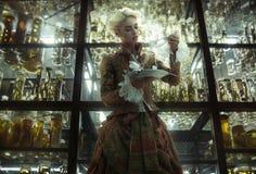 Begreppsmässig bild av den retro damen i det gamla laboratoriumet Royaltyfri Foto