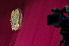 Begreppsnyheterna Vapensköld av Republikenet Kazakstan på en röd bakgrund Televisionkameran i det unfocused som in göras suddig arkivfoto