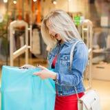 Begreppsshopping Ståenden av den blonda kvinnan för skönhet i tillfällig kläder som förvånar köp nära, shoppar i shoppingen Royaltyfri Bild