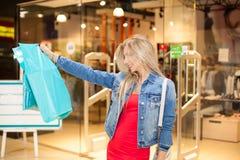Begreppsshopping Ståenden av den blonda le kvinnan för skönhet i tillfälliga hållande shoppingpåsar nära shoppar i shoppingen Arkivbild