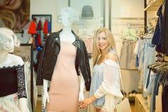 Begreppsshopping Ståenden av skönhet som ler kvinnan shoppar in och att välja kläder på attrapp inomhus Arkivfoton