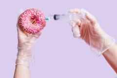 Begreppsskräpmat Händer, injektionsspruta och rosa munk arkivfoto