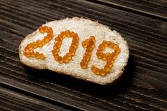 Begreppssmörgås med 2019 år som göras av den röda kaviaren royaltyfri fotografi