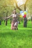 begreppssoffa som tycker om den moderna nätt vita kvinnan för livsstil Ung Caucasian blond kvinnlig med gruppen av luftballonger Arkivfoto