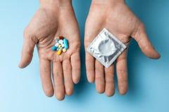 Begreppsval av det att använda preventivmedel, pillret eller kondomen Mannen i hans hand är födelsekontrollpiller och i den begag arkivbild