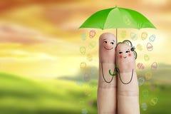 Begriffs-Ostern-Fingerkunst Paar hält grünen Regenschirm mit fallenden Ostereiern Auf lagerbild Lizenzfreie Stockfotografie