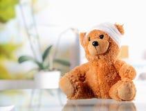 Begriffs-Teddy Bear mit Verband auf dem Tisch stockfotografie
