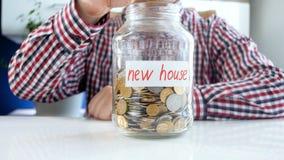 Begriffs-Video 4k des sammelnden und Rettungsgeldes des jungen Mannes für das Kaufen des neuen Hauses stock video