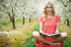 Begriffsbild der Blondine ein Buch im Obstgarten lesend Lizenzfreie Stockfotos