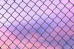 Begriffsbild des Dämmerungshimmels mit Effekt des hellen Pastelltones und des Stahlmaschendrahtzauns lizenzfreies stockbild
