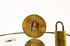 Begriffsbild einer cryptocurrency goldenen bitcoin Münze auf einer weißen Spiegeloberfläche mit einem goldenen Vorhängeschloss- u stockfotos