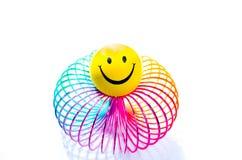 Smiley auf einem schleichenden Spielzeug des Regenbogens Lizenzfreie Stockfotografie
