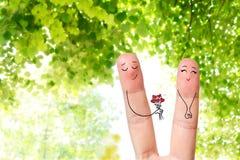 Begriffsfingerkunst eines glücklichen Paars Mann gibt einen Blumenstrauß Auf lagerbild Lizenzfreie Stockfotografie