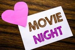 Begriffshandschrifttext, der Film-Nacht zeigt Konzept für Wathing-Filme geschrieben auf klebriges Briefpapier, hölzerner hölzerne lizenzfreies stockfoto
