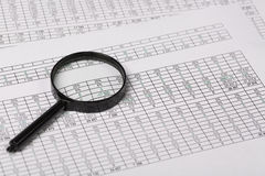 Begriffslupe auf Berichten mit Zahlen Stockfotos