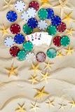 Begriffssand mit Sternen, Pokerchips und Karten Stockfotos