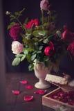 Begriffsstillleben-Rosen in einem Weinlese-Vase Stockfotos