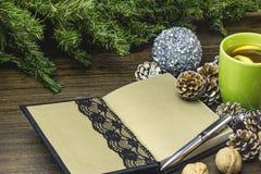 Begriffszusammensetzung auf einem Holztisch mit einer Tasse Tee, ein handgemachtes Notizbuch, Tannenzapfen Lizenzfreie Stockfotografie