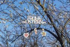 Begroetend Gelukkige Pasen in het Duitse hangen op bloeiende boom, op heldere blauwe hemelachtergrond De lentevakantie Stock Fotografie