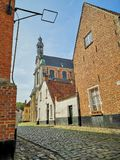 The beguinage and the St. Margaret`s church in Lier, Belgium. The Saint Margaret`s Church and old houses in the Unesco protected beguinage in the city center of stock photo