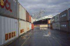 Behälter auf Versand koppeln mit Schiff im Hintergrund an Lizenzfreie Stockfotografie