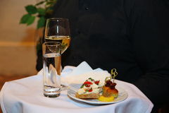 Behälter, bedeckt mit einer weißen Tischdecke, mit einem Glas Wein, takan mit Wasser und einer Platte von Snäcken in der Hand des Stockbild