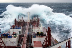 Behälter in den schweren Meeren Stockfotos