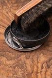 Behälter der Schuhcreme und des Pinsels auf hölzernem Stockbild