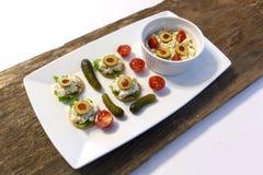 Behälter des Thunfischs auf Crackern mit Essiggurken und Tomaten Lizenzfreie Stockfotografie