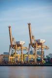 Behälter-Frachtfrachtschiff mit Arbeitskranbrücke in der Werft an der Dämmerung für logistischen Import-export Lizenzfreies Stockbild