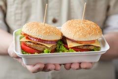 Behälter mit Burgern in den männlichen Händen Stockfotografie