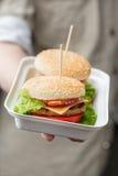 Behälter mit Burgern in der männlichen Hand Lizenzfreie Stockfotos