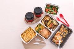 Behälter mit geschmackvollen zum Mitnehmen Mahlzeiten auf hellem Hintergrund, Draufsicht Lebensmittellieferung stockfoto