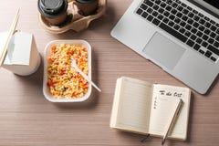 Behälter mit köstlichen Mahlzeiten, Notizbuch und Laptop auf Tabelle Konzept der Nahrungsmittellieferung online stockfotografie