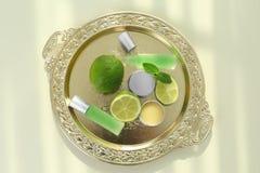 Behälter mit Parfümen, Kalken und tadellosen Blättern stockfoto