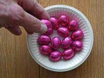 Behälter mit violetten chocolade egss dargestellt während des Ostens lizenzfreies stockfoto