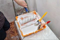 Behälter mit weißen Farben- und Malereiwerkzeugen, Rolle und Bürsten Lizenzfreie Stockfotos