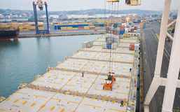 Behälteroperation im Hafen mit Kränen und Bockladen/Entladungsbehältern Stockfotos