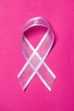 behåbröstcancerbegrepp som klipper rosa sax Rosa band på färgbakgrund Royaltyfri Bild