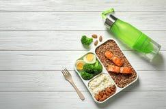 Behållare med naturlig sund lunch, flaskan av vatten och utrymme för text på tabellen, bästa sikt Högt - proteinmat royaltyfri foto